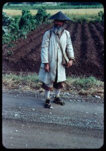 Bearded man in a long coat on a country road